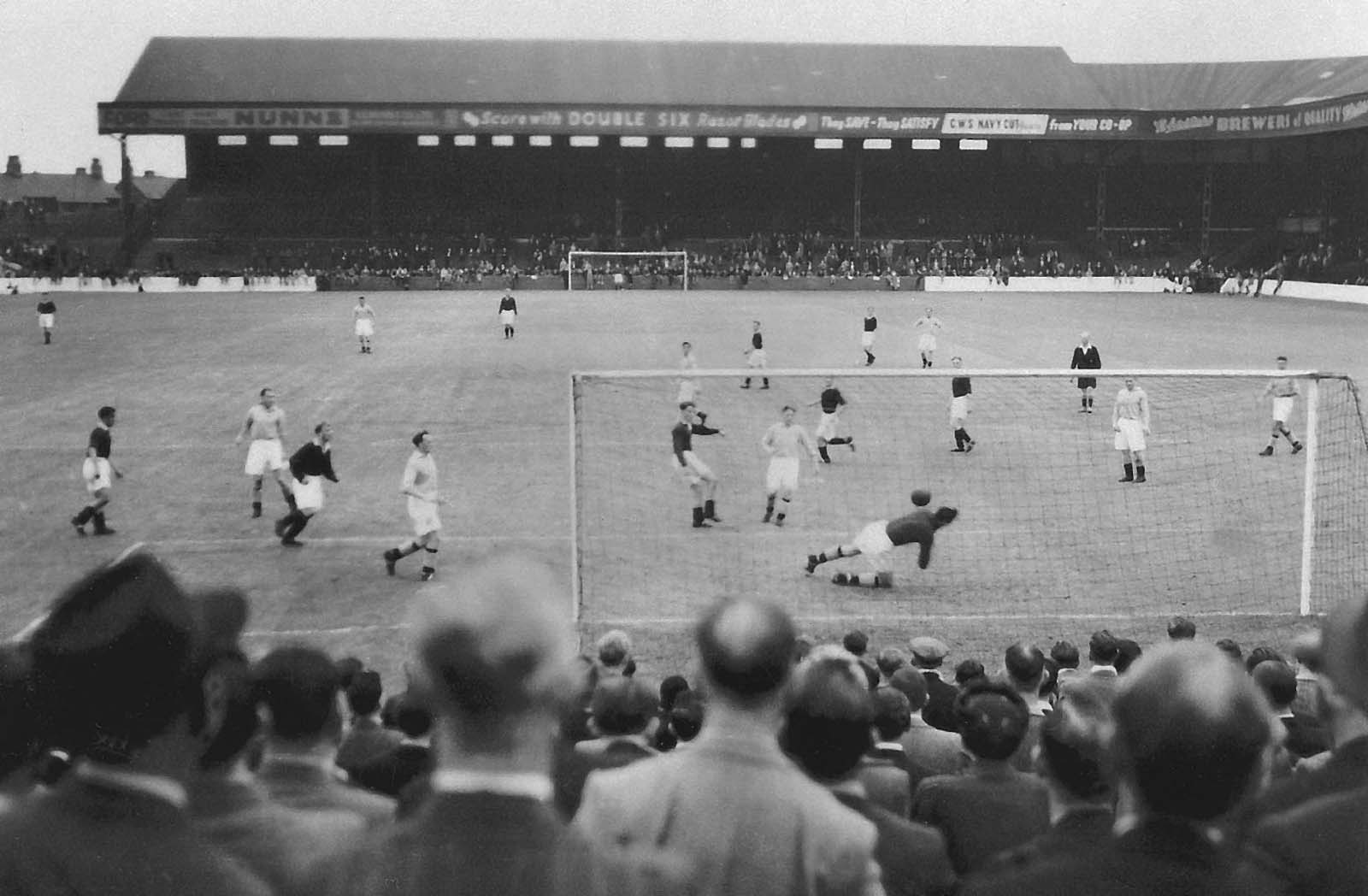 balck and white photo taken across the heads of a crowd ina football terrace watching a goal mouth scramble on the football pitch
