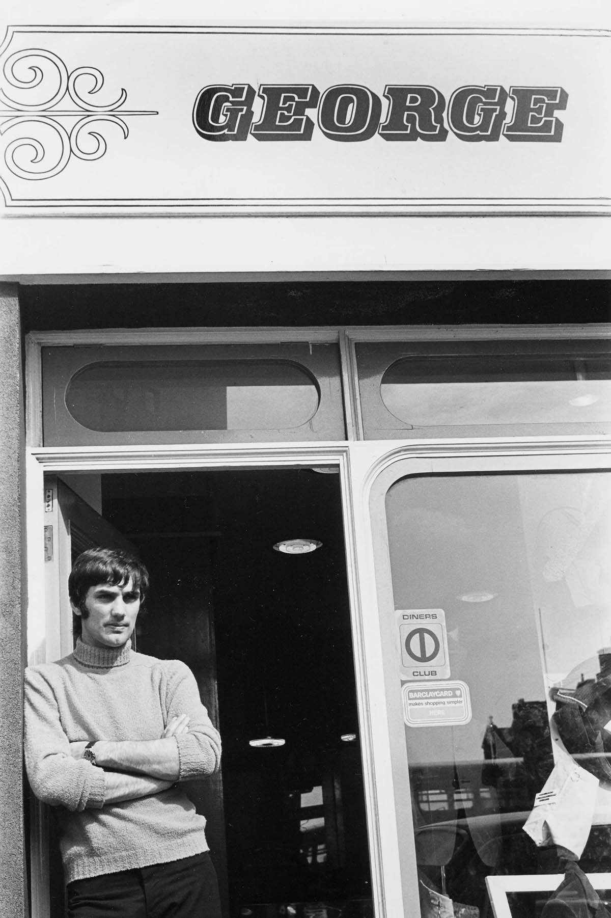 photo of a man in roll neck sweater and longish heair leaning against the door of a shop