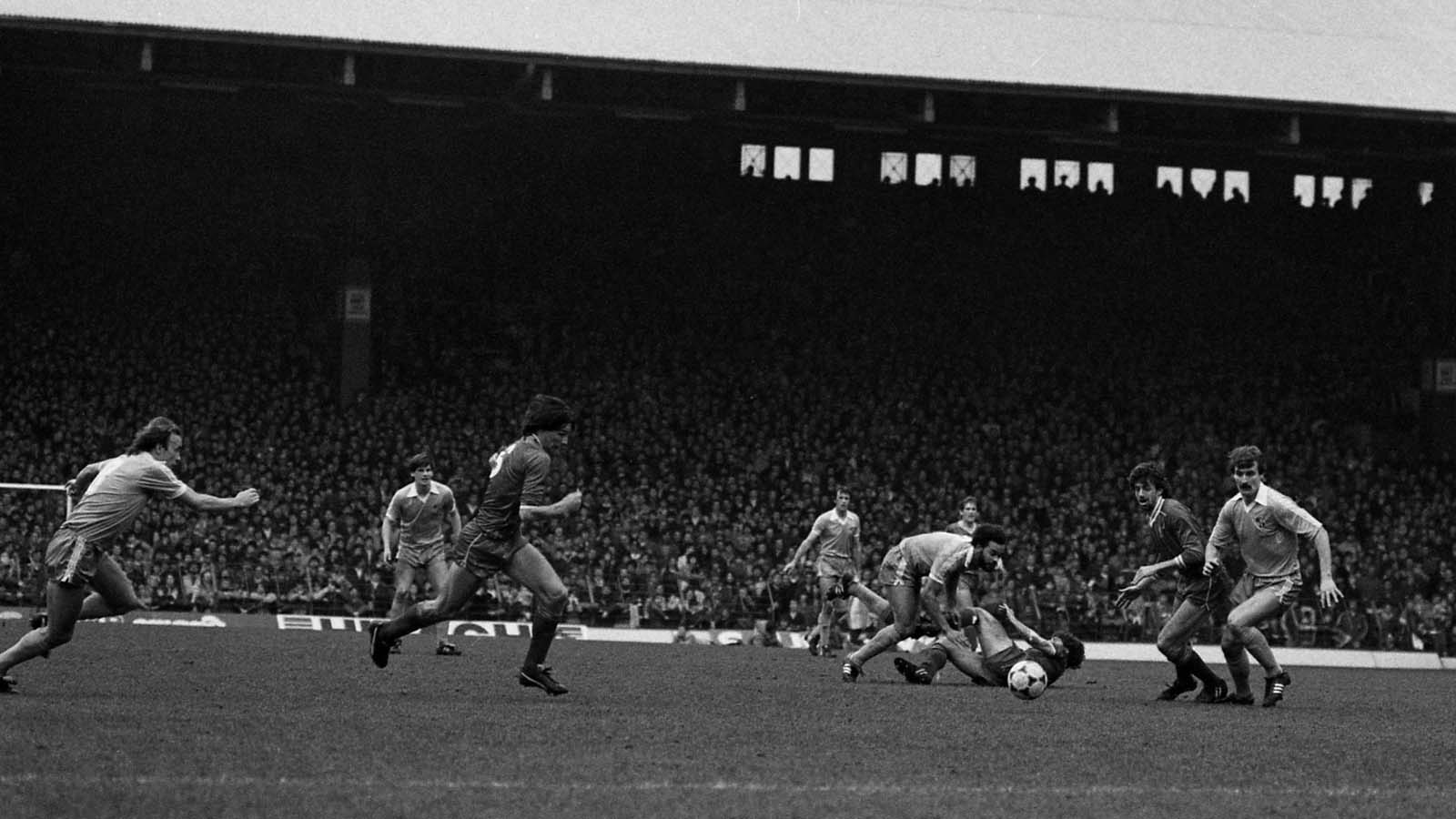 black and white photo of players running towards a ball during a football match