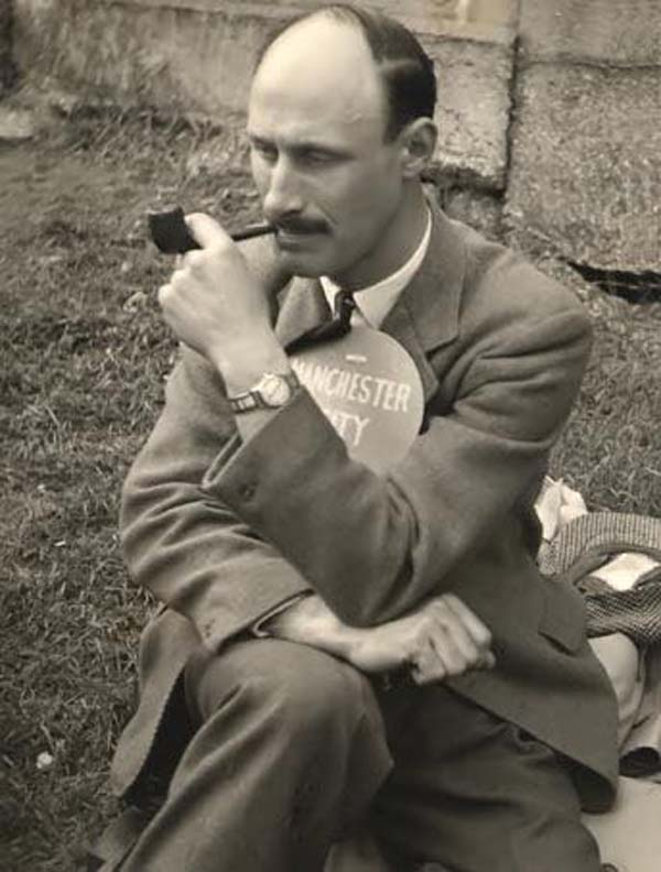 black and white photo of a seated man with bald head seated with crossed legs smoking a pipe