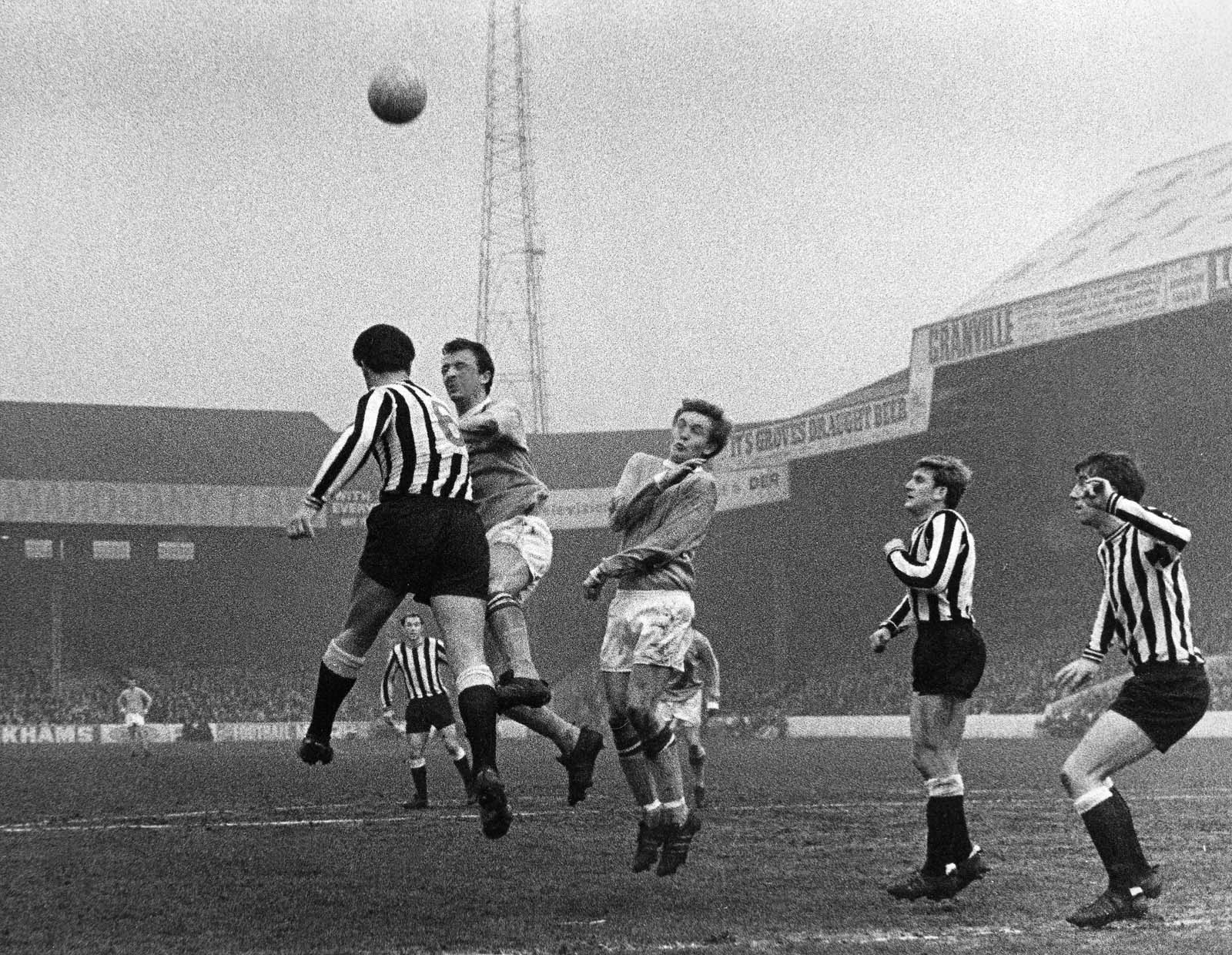 black and white photo of footballers jumping for a ball in a goal nouth