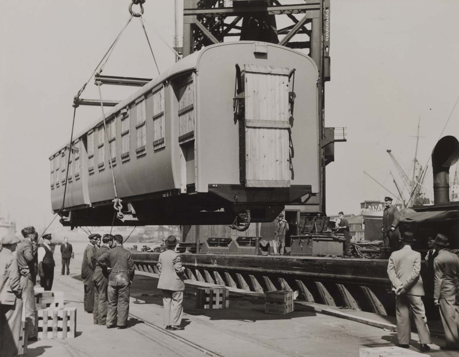 photo of a railway carriage being craned onto the side of a dock