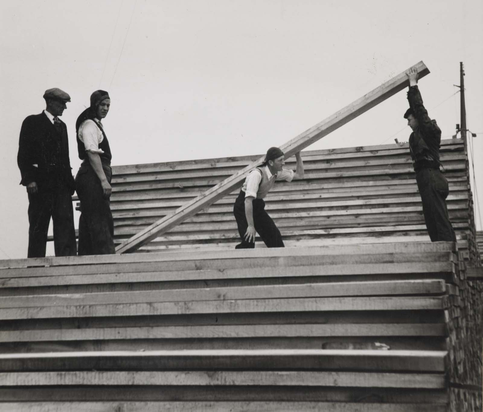 photo of a man carrying a large beam watched by other men