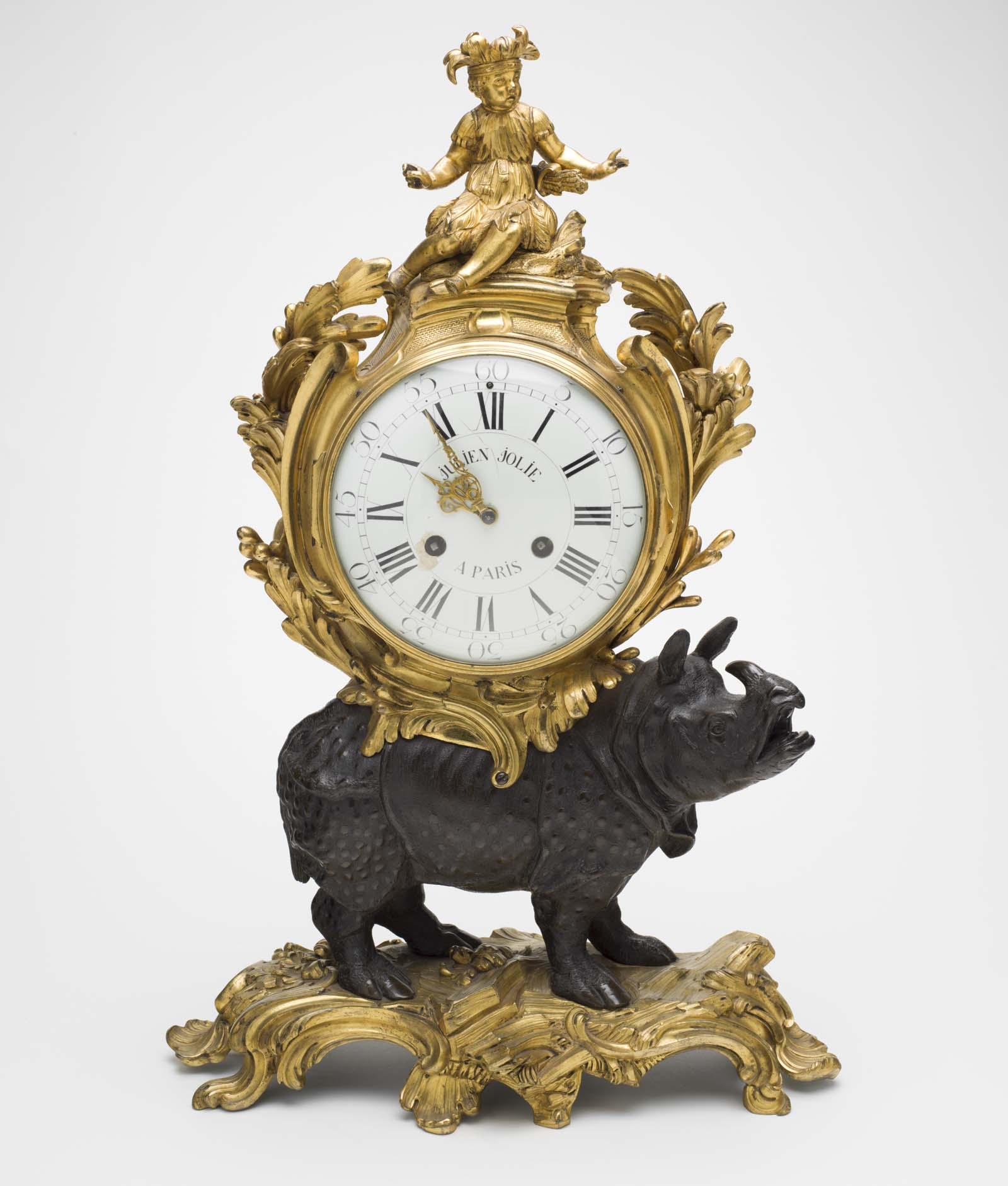 ornate gold clock mounted onto a black porcelain rhino on a gold stand