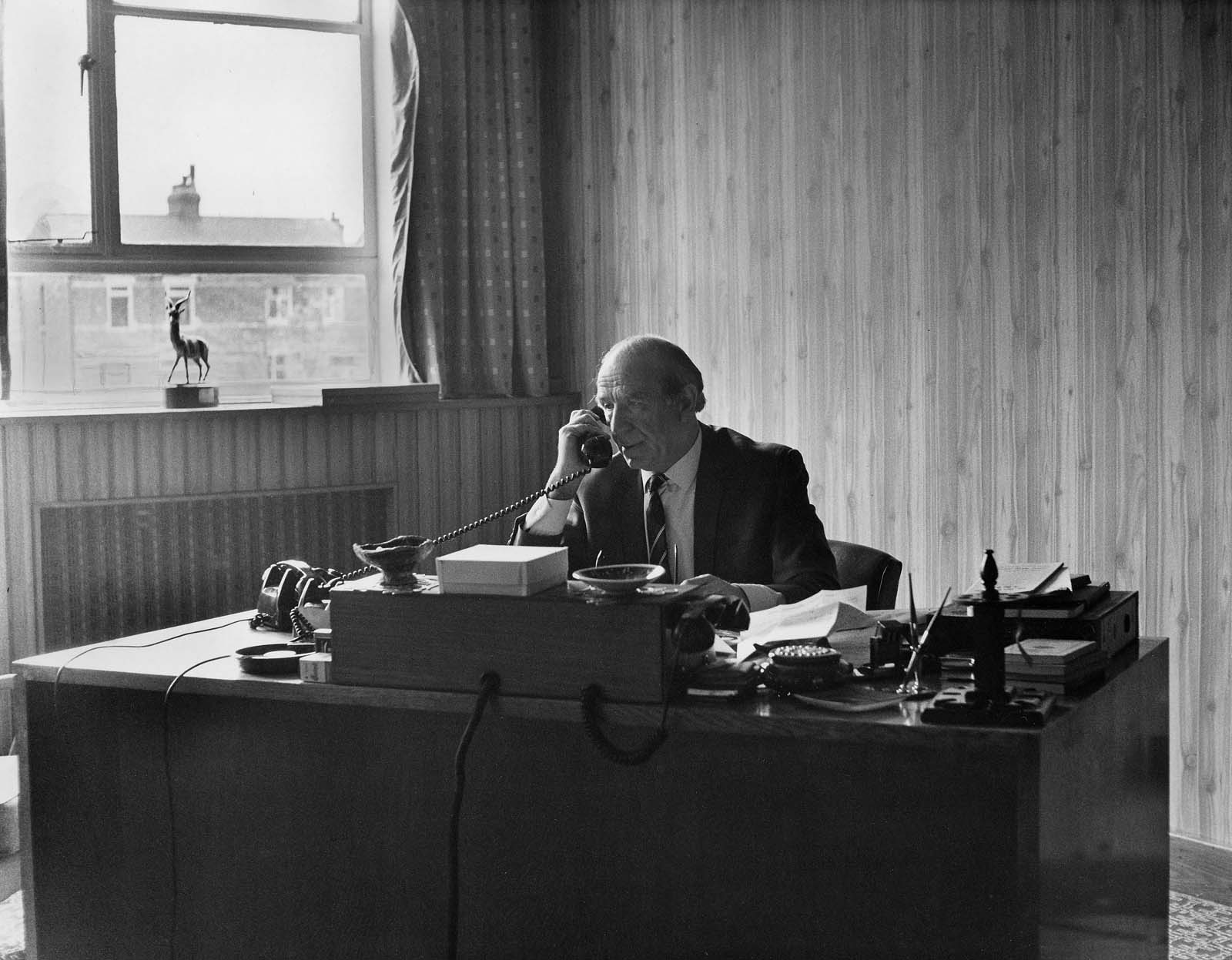 black and white photo of a man speaking on the phone at deskin an office with wallpaper behind him