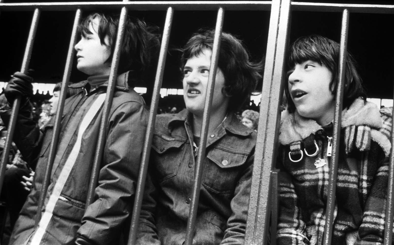 black and white photos of young lads in sevties clothes pressed against the railings of a football terrace
