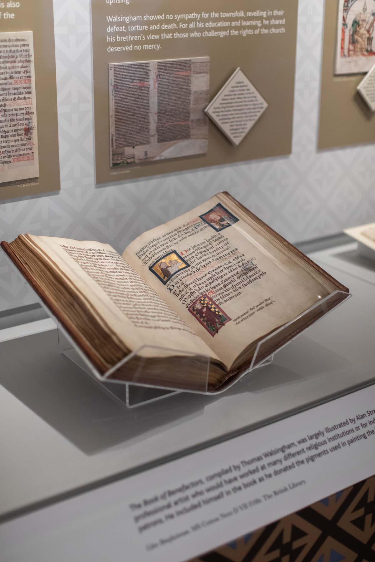 photo of an open book of medieval text and illustration on display in a case