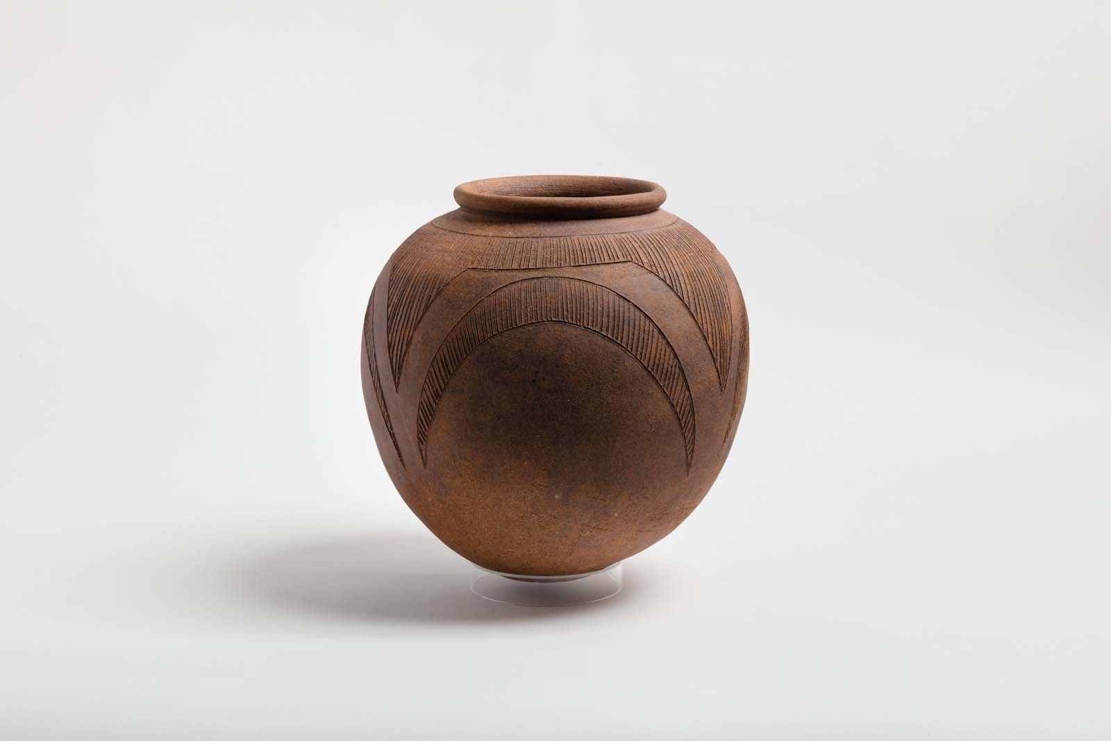 photo of a large terracotta pot with simple incised decoration