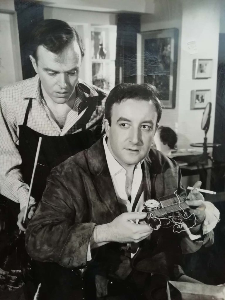 film still showing Kenneth Graham and Peter Sellers who is wearing a silk dressing gown