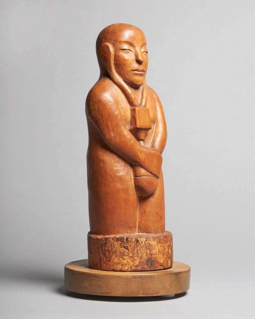 a carved wooden figure with arms crossed