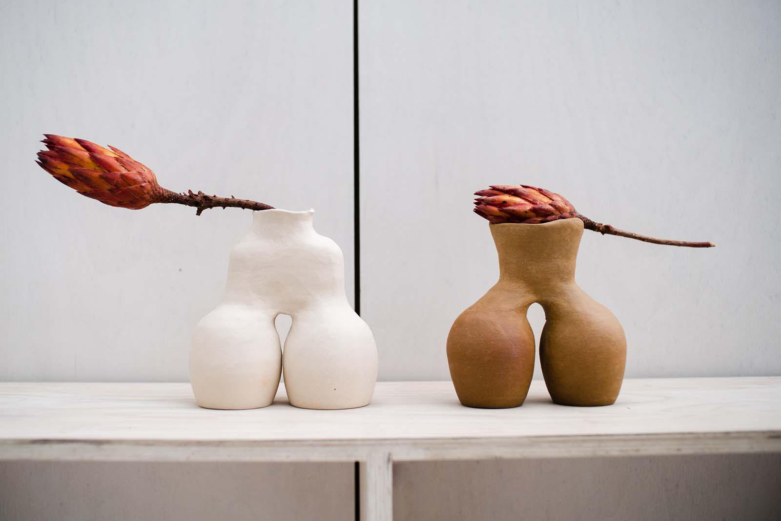 photo of a white and terracotta coloured pair of vessels each with bulbous stands and single mouth