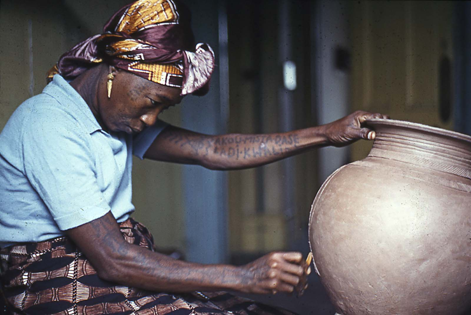 photo of an African woman adding decoration to the outside of a pot