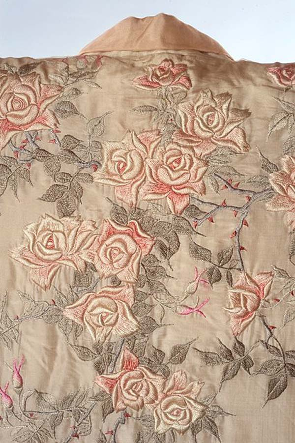 close up detail of a pink fabric with rose motifs