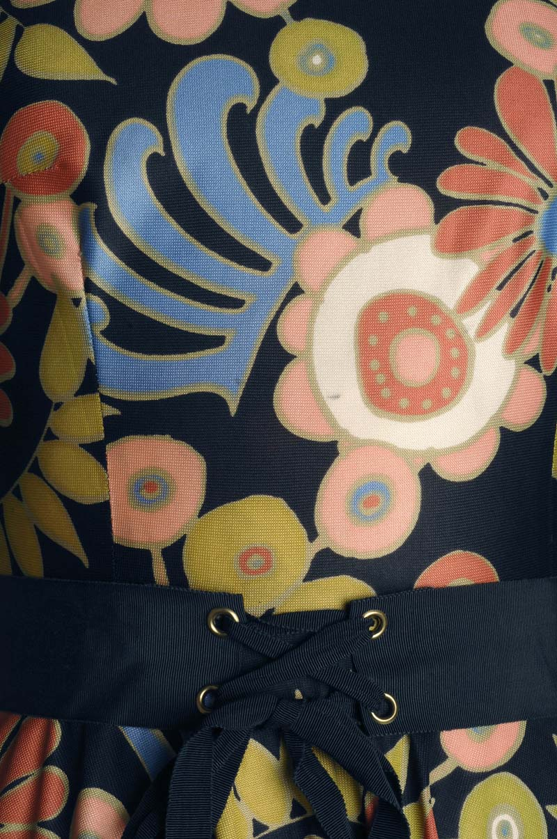 close up of 70s style flowers against a black fabric background
