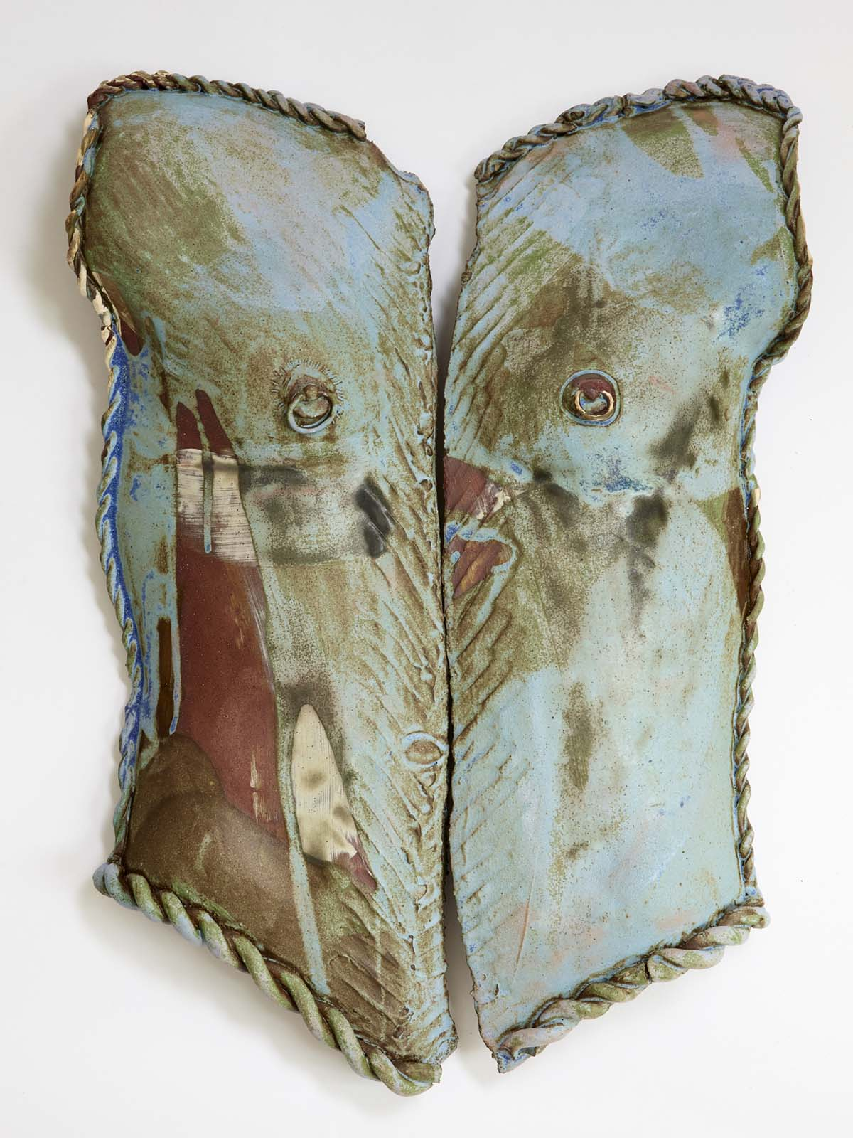 a ceramic male torso in two parts