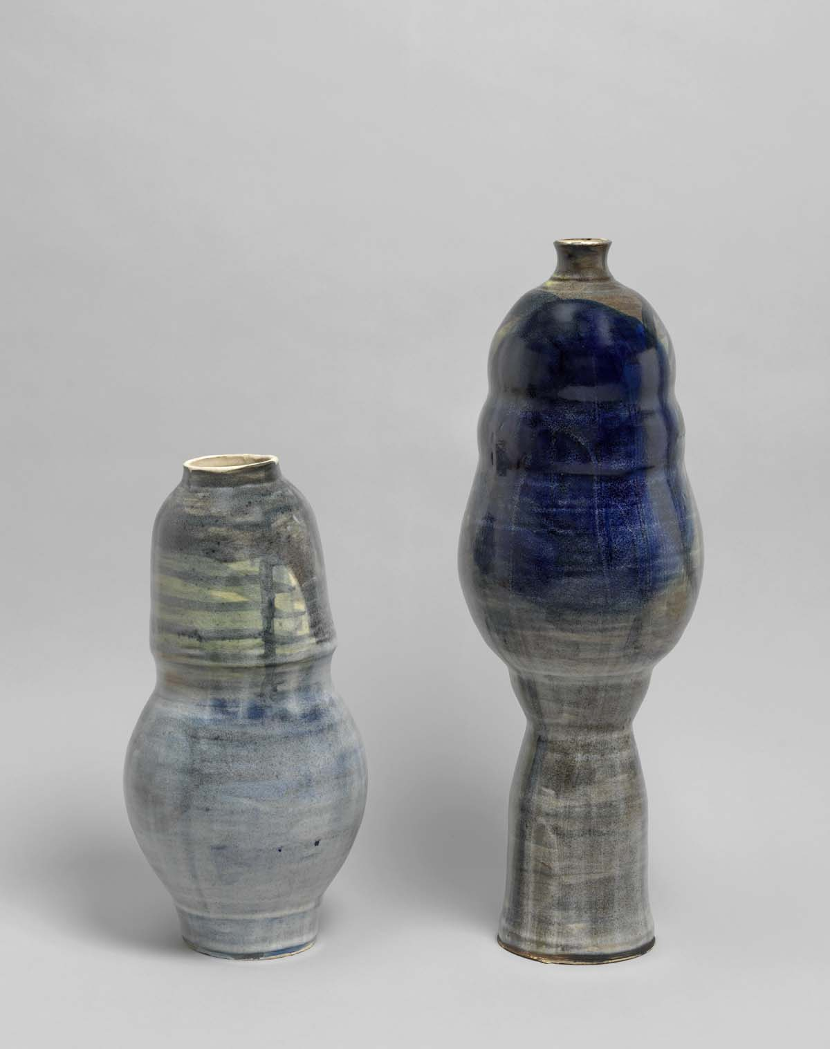 a pair of ceramic pieces in blue and green with conical yet bulbous shape