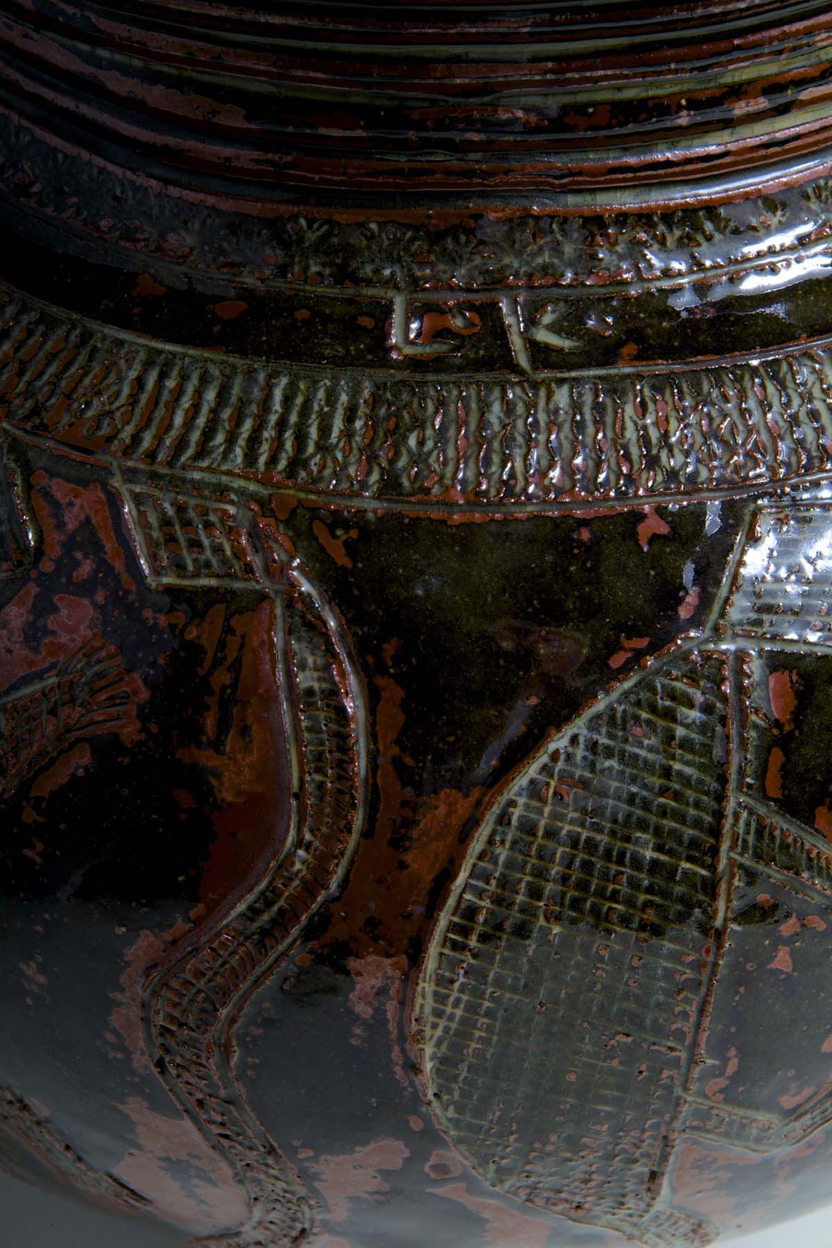 close up of incised fish detail and other decoration on a glazed pot