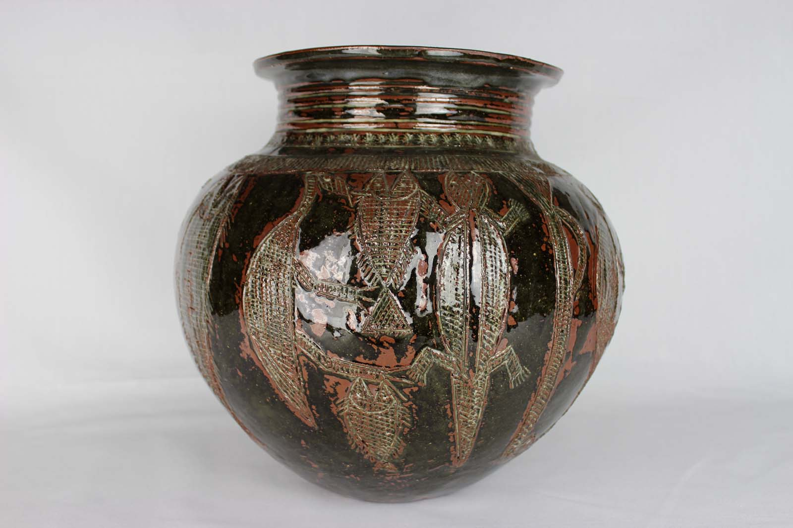 photo of an earthenware pot with crocodile and fish motifs